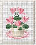Cross stitch of pink cyclamen flowers in a white pot.
