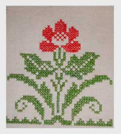 Simple cross stitch of a geometric flower in red and green.